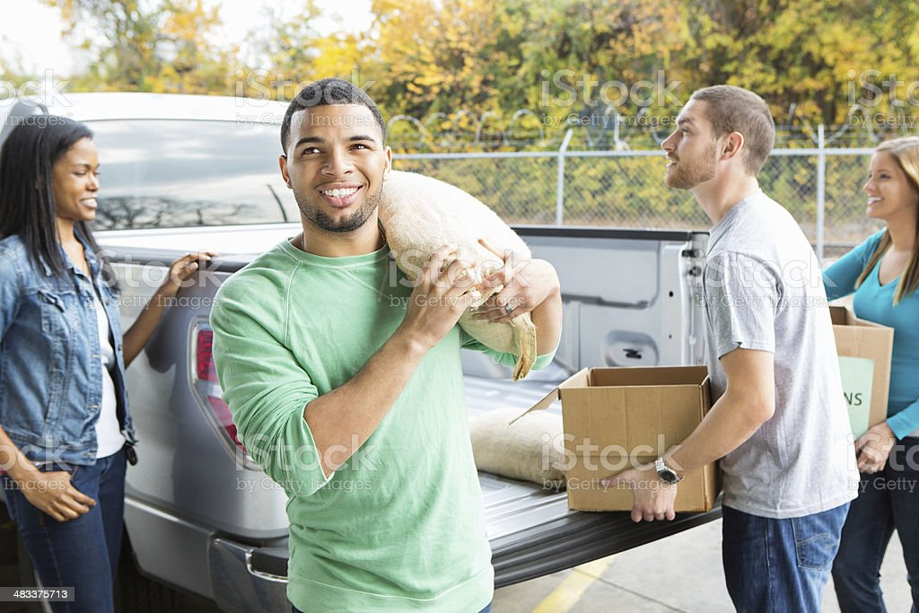 Volunteers unloading donations of groceries outside food bank stock photo