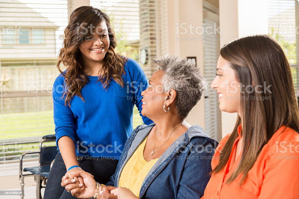 Volunteers visit with senior woman, grandmother in her home. stock photo