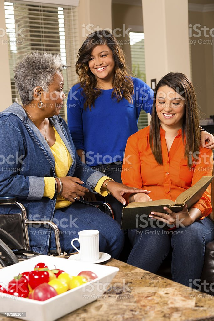 Volunteers visit with senior woman in her home. stock photo