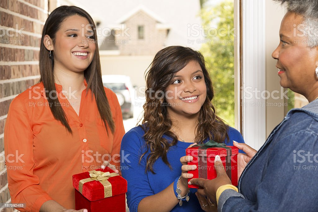 Volunteers:  Young adults bring Christmas gifts to senior woman. stock photo