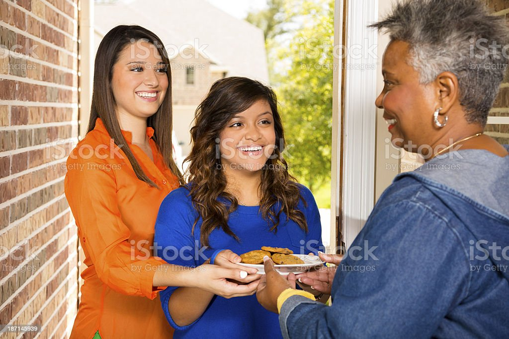 Volunteers:  Young adults bring cookies to senior woman. stock photo