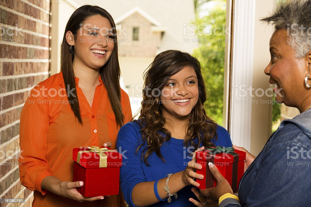 Volunteers:  Young adults bring gifts to senior woman. royalty-free stock photo