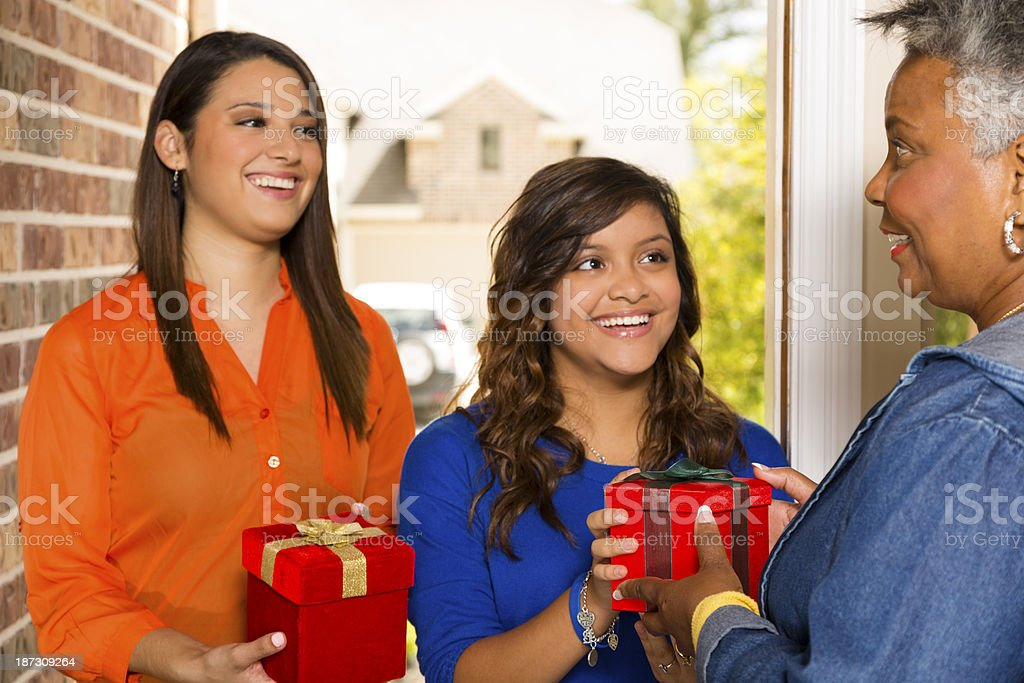 Volunteers:  Young adults bring gifts to senior woman. stock photo