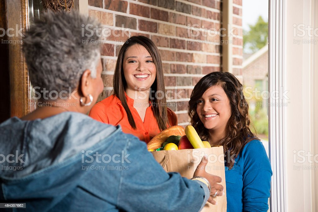 Volunteers:  Young adults bring groceries to senior woman at home. stock photo