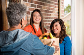 Volunteers:  Young adults bring groceries to senior woman at home.