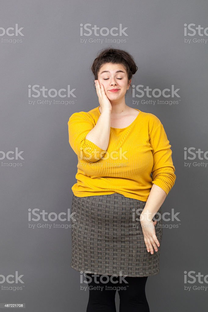 voluptuous 20s girl reinsuring herself in daydreaming stock photo