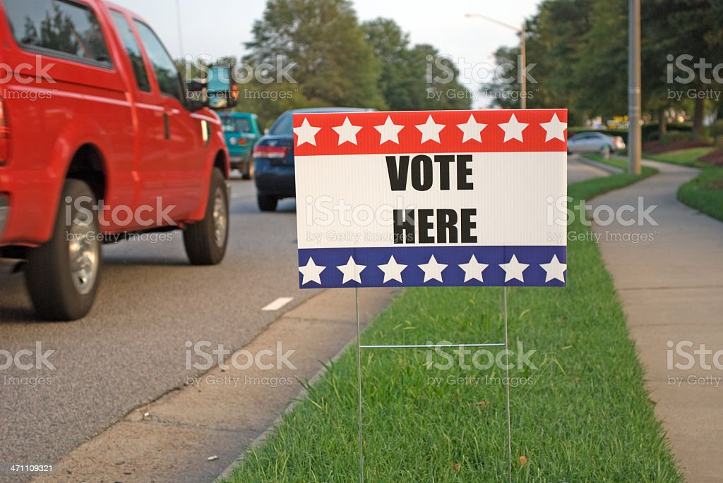 Vote Here Sign with cars passing by.. royalty-free stock photo