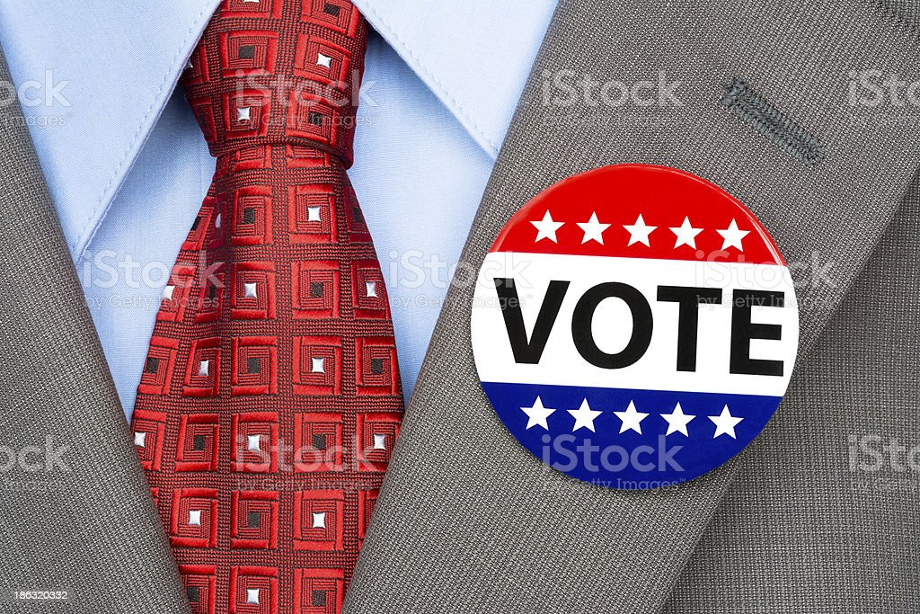 Vote pin on brown suit stock photo
