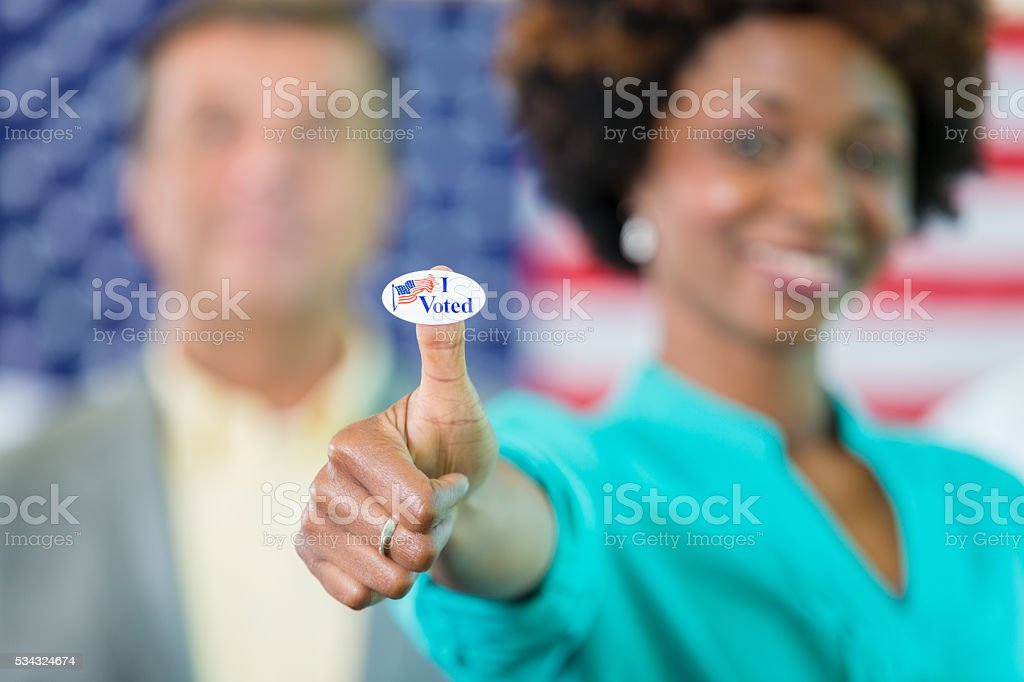Voter gives a thumbs up with I voted sticker stock photo