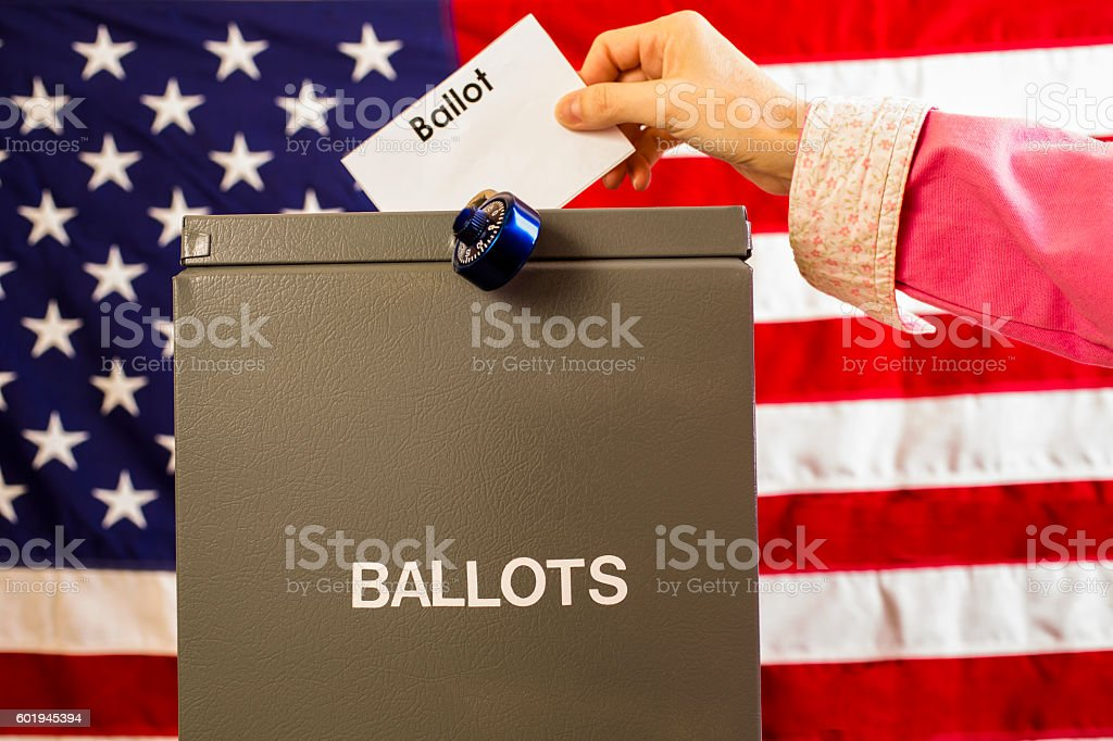 Voter inserting ballot into box with USA flag background. stock photo