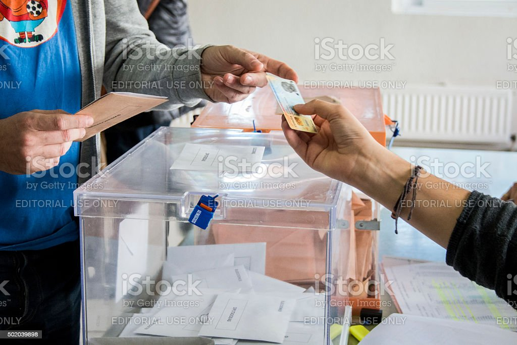 Voter showing his Identity Card next to electoral urns stock photo