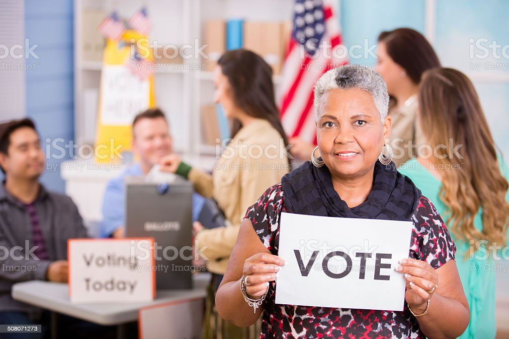 Voters register, voting in USA elections. Woman holds 'Vote' sign. stock photo