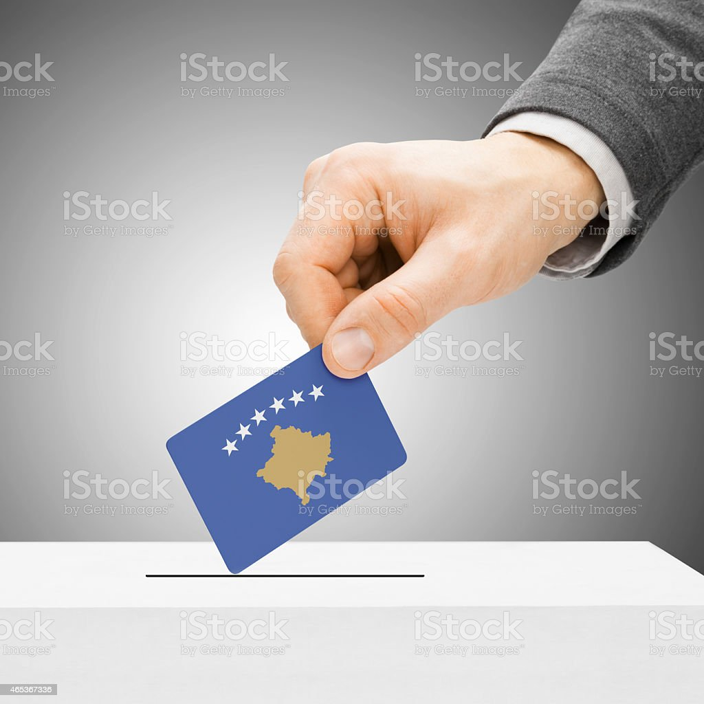 Voting - Male inserting flag into ballot box - Kosovo stock photo