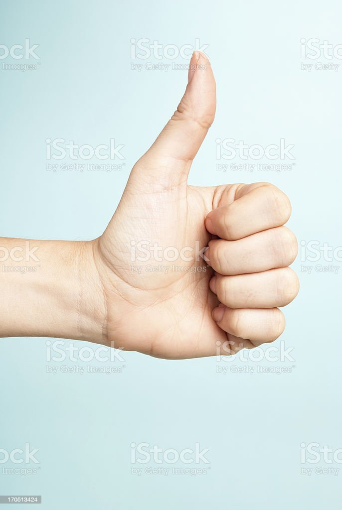 Voting. Woman hand making like gesture on blue background. stock photo