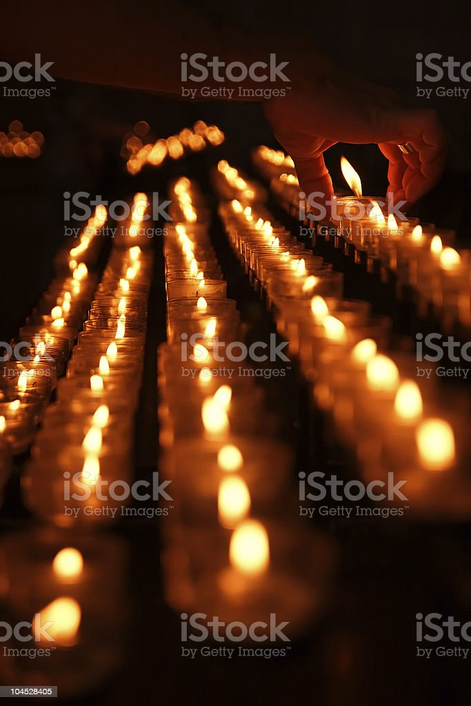 Votive candle placed by man\\'s hand royalty-free stock photo