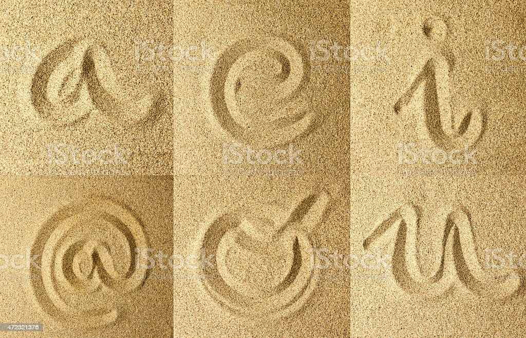 vowels and arroba handwritten in the sand stock photo