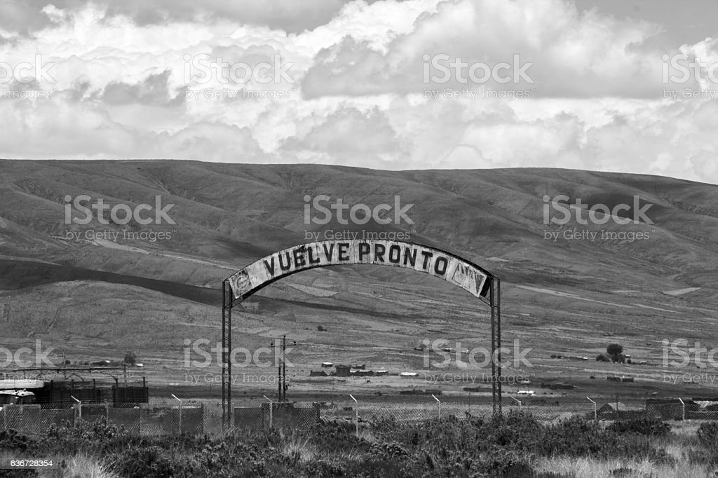 'vuelve pronto' (come back soon) sign next to some hills stock photo