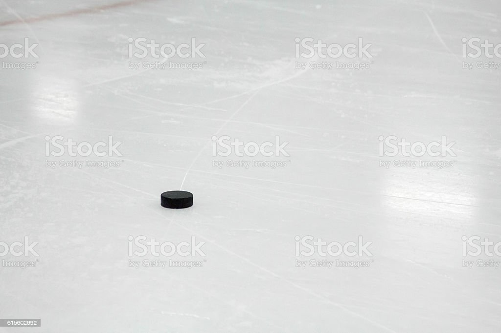 Vulcanized rubber puck on the ice of an arena stock photo