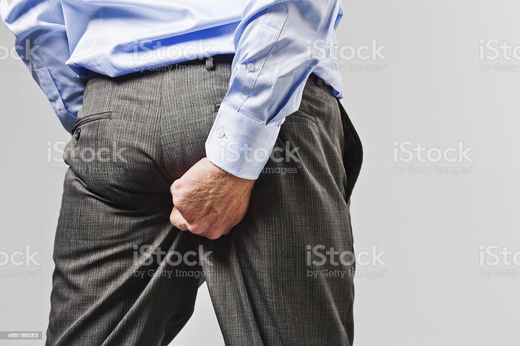 Vulgar businessman scratches his bottom stock photo