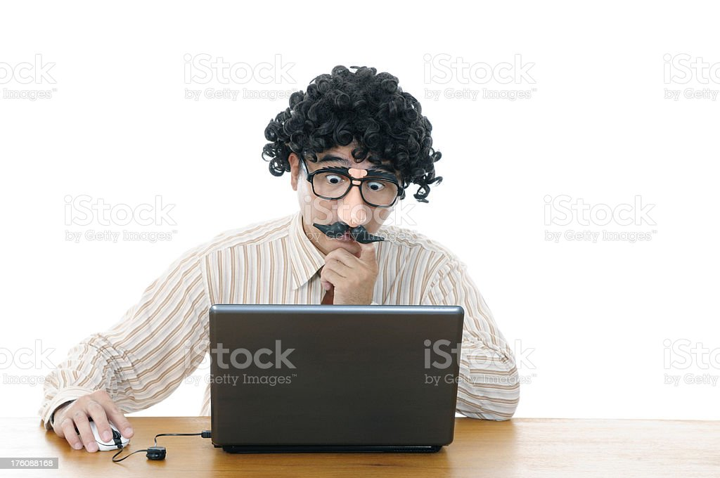 Wacky man with comedy eyeglasses and wig using a laptop stock photo