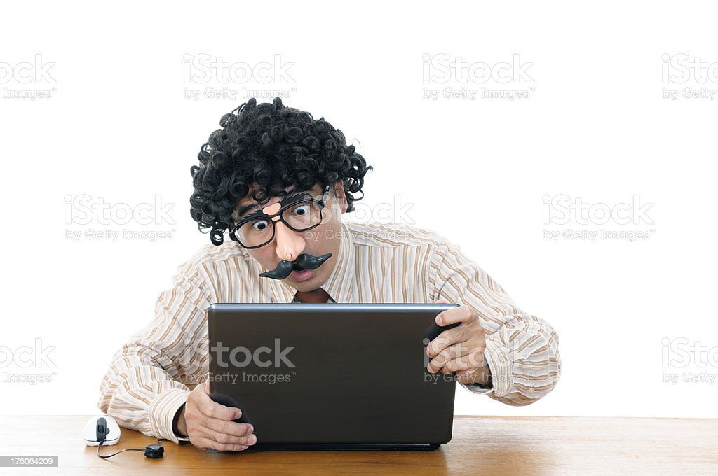 Wacky man with comedy eyeglasses and wig viewing a laptop stock photo