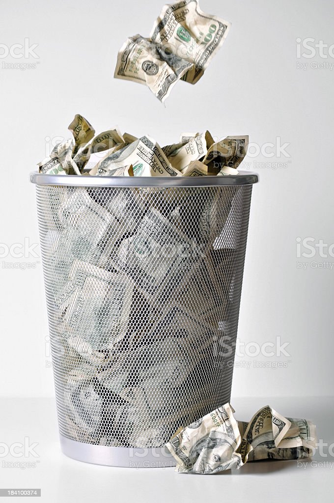 Wadded Up Money Being Thrown into a Trashcan stock photo