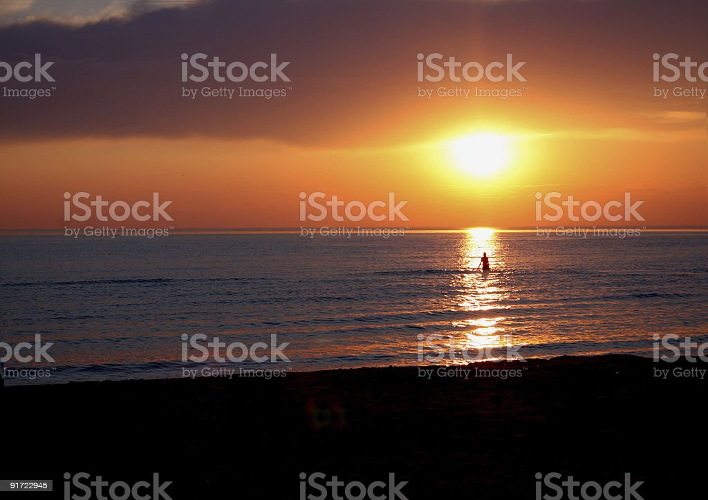 Wading into the sunset. stock photo