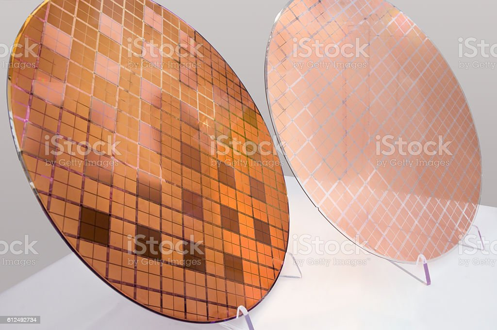 Wafer with elements in Flip-Chip-Montage (left) and processed glass wafer stock photo