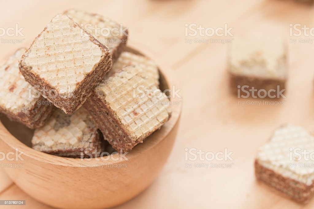 Wafers with chocolate in cup on wooden background. stock photo