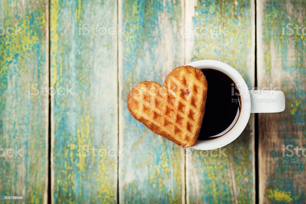 Waffle biscuits in shape of heart with coffee, top view stock photo