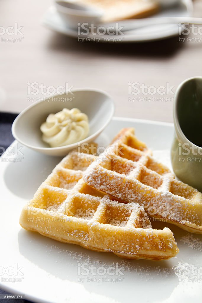 waffle with icing sugar, butter, syrup stock photo