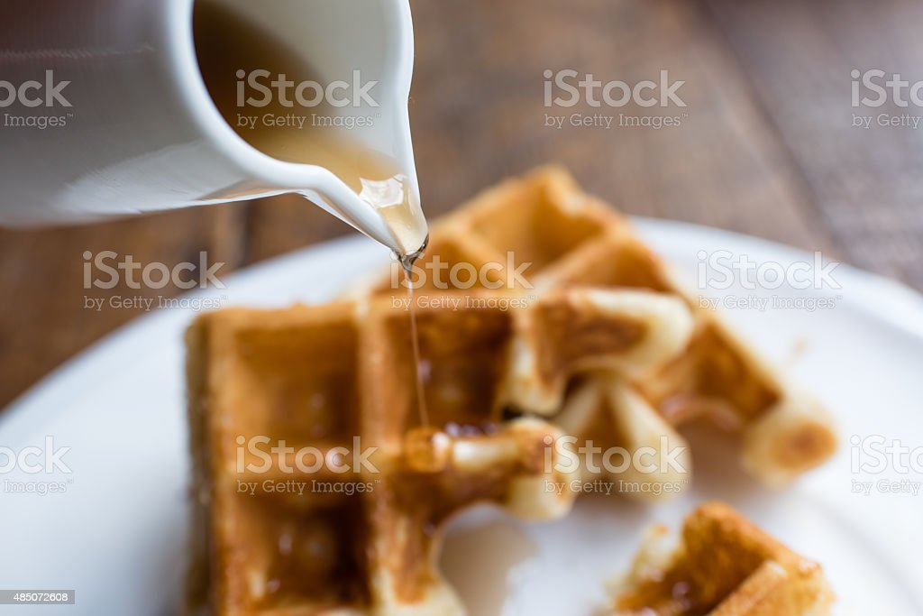 Waffle with Pouring Maple Syrup stock photo