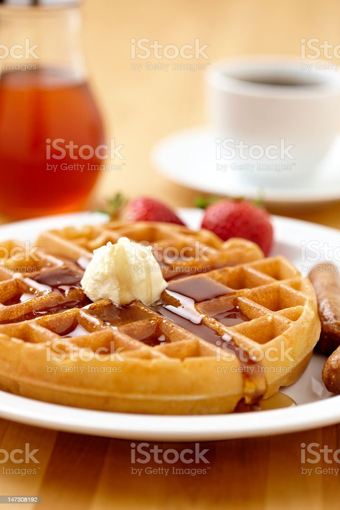 Waffle with syrup, strawberries, and sausage links stock photo