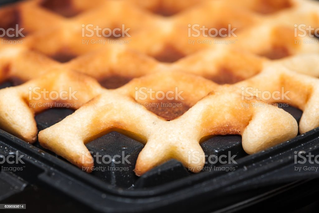 waffles are cooked in waffle iron stock photo