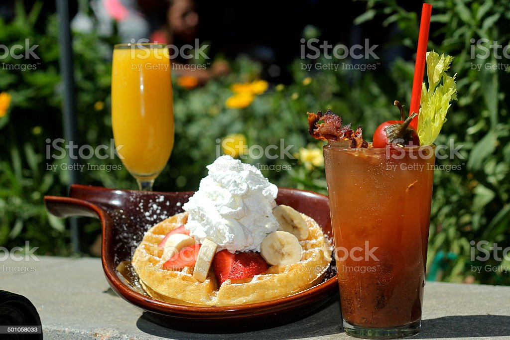 Waffles with Bananas, Strawberries, Whip Cream, Bloody Marys, Mimosas Alfresco stock photo