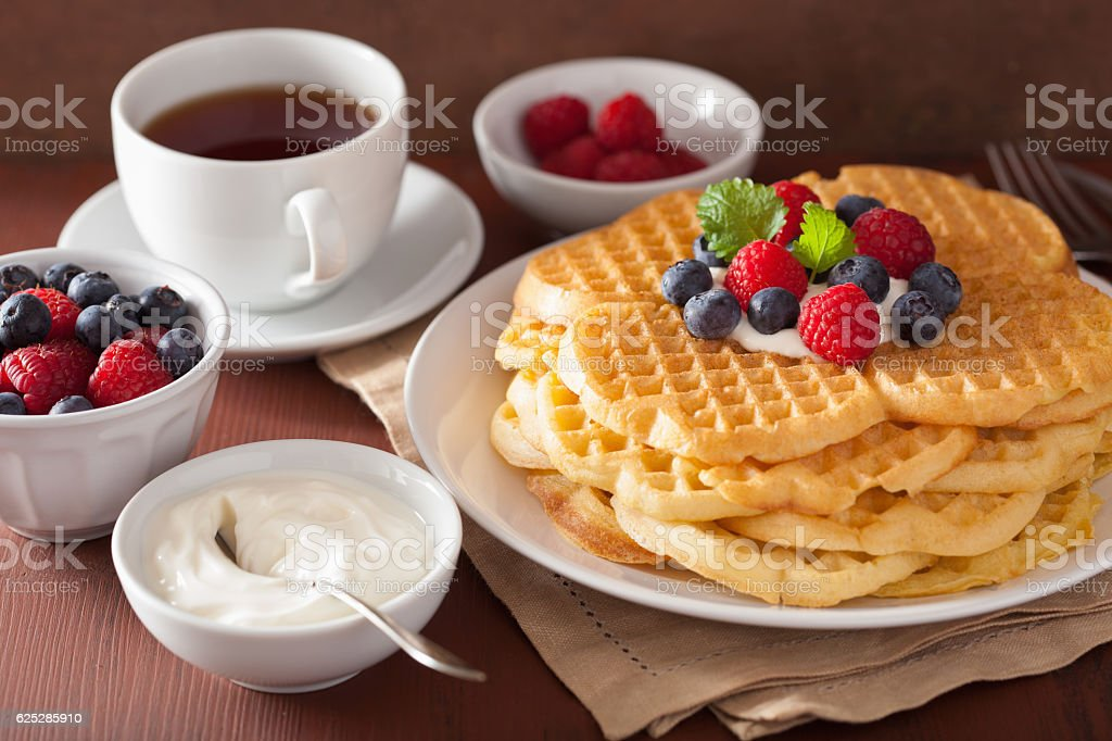 waffles with creme fraiche and berries for breakfast stock photo