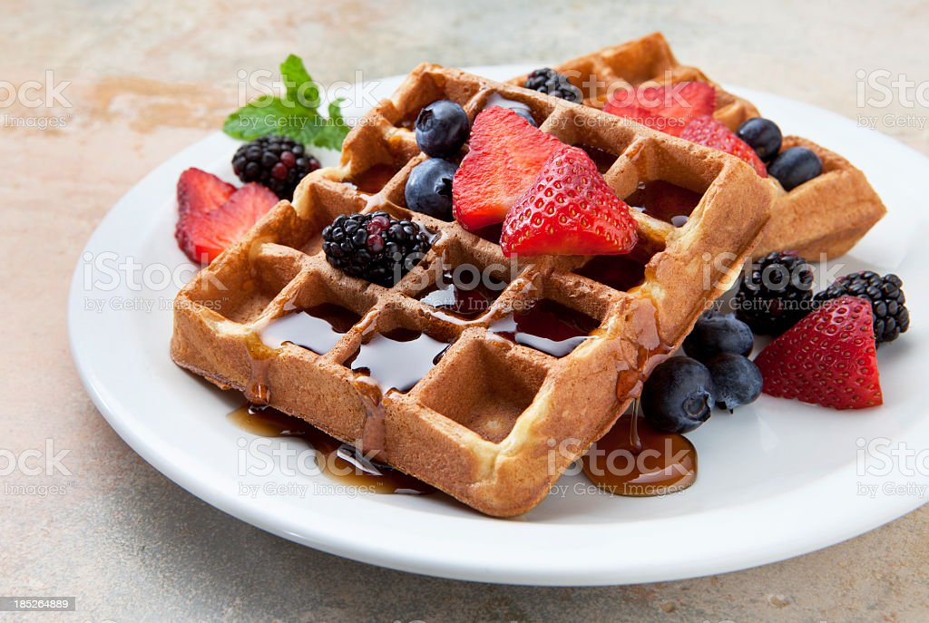 Waffles with fruit and maple syrup on a marble counter. royalty-free stock photo