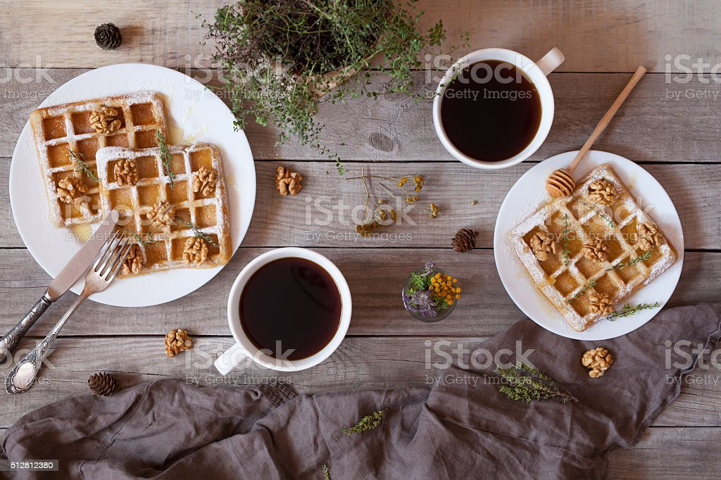 Waffles with honey, nuts, coffee and herbs, sweet dessert breakfast. stock photo