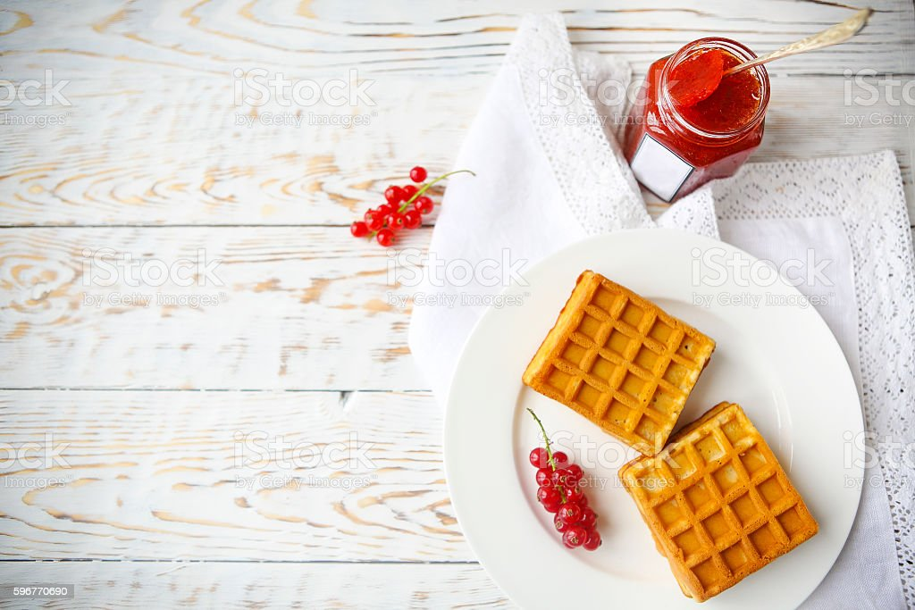 Waffles with red currant jam and berries on white plate stock photo