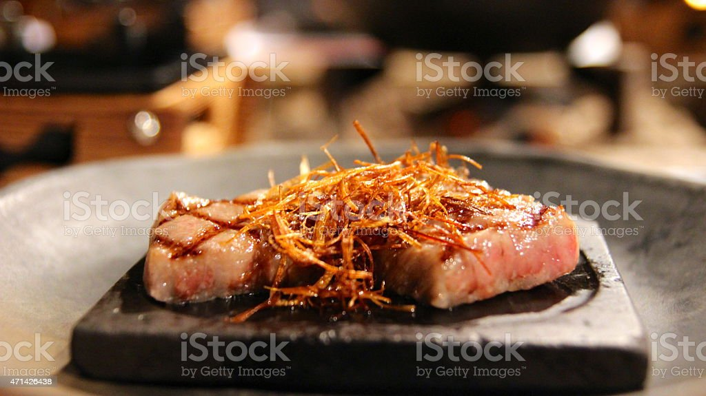 wagyu beef steak on hotplate with fried onion stock photo