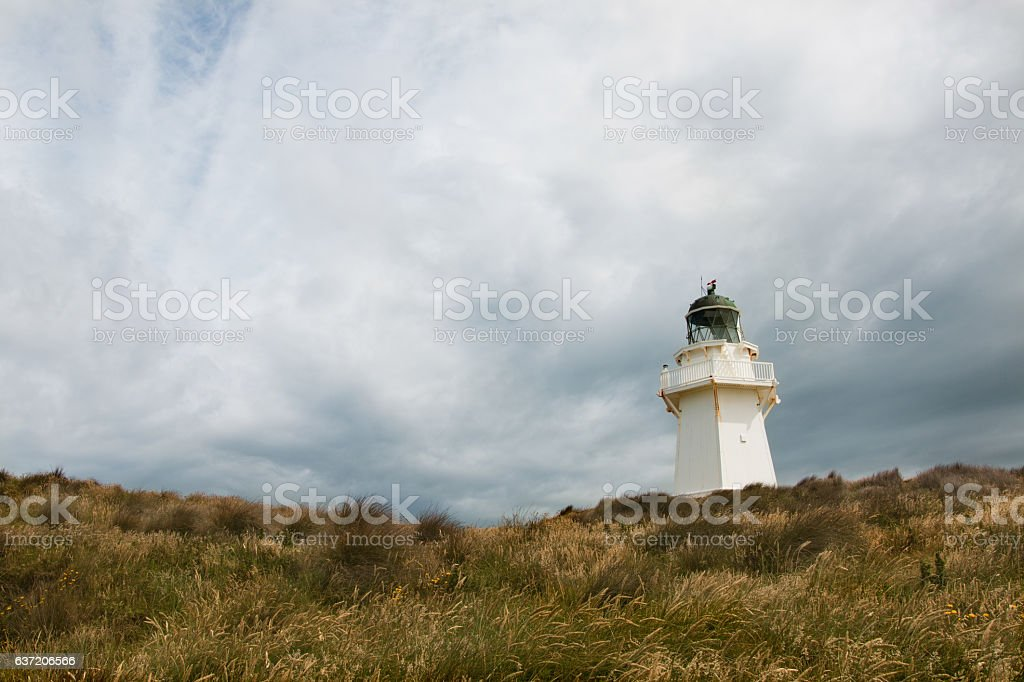 Waipapa Point lighthouse with background of cloudy sky stock photo