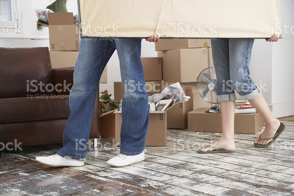 Waist down man and woman carrying picture in home with cardboard boxes royalty-free stock photo