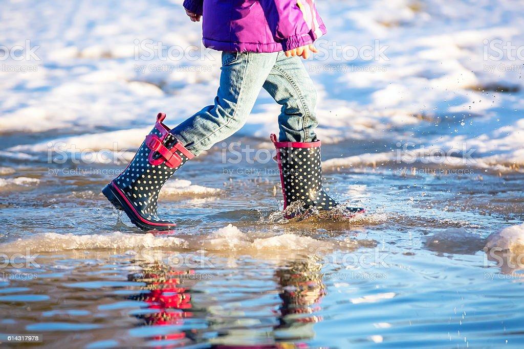 Waist Down of Child Walking Through Springtime Puddle stock photo