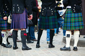 Waist down view of a group of men in traditional kilts