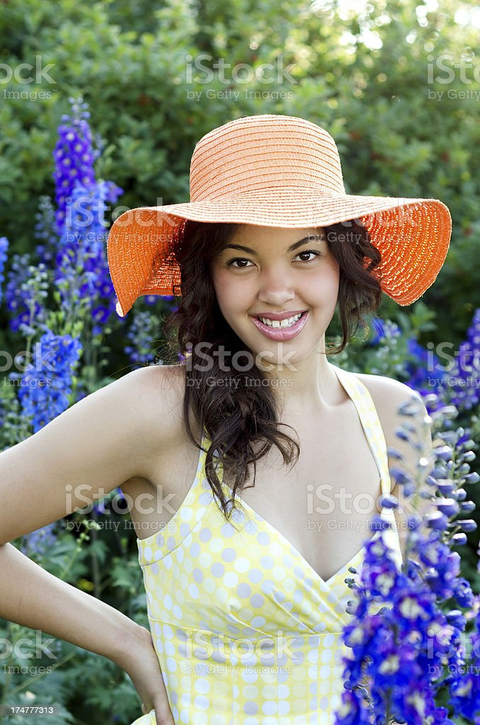 Waist up of smiling teen amid delphiniums royalty-free stock photo