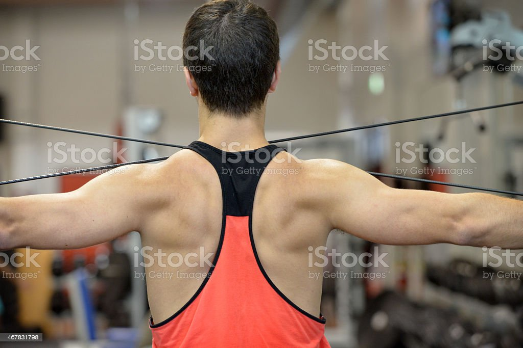 Waist up rear view of young man doing weights stock photo