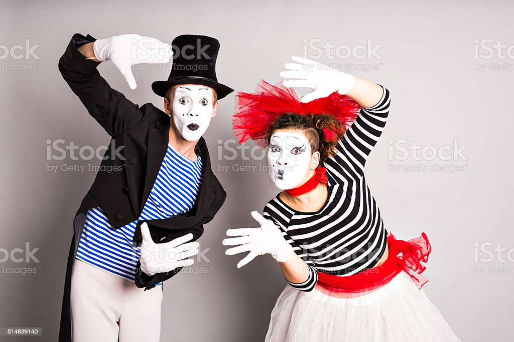 Waist-up portrait of funny mime couple with white faces stock photo