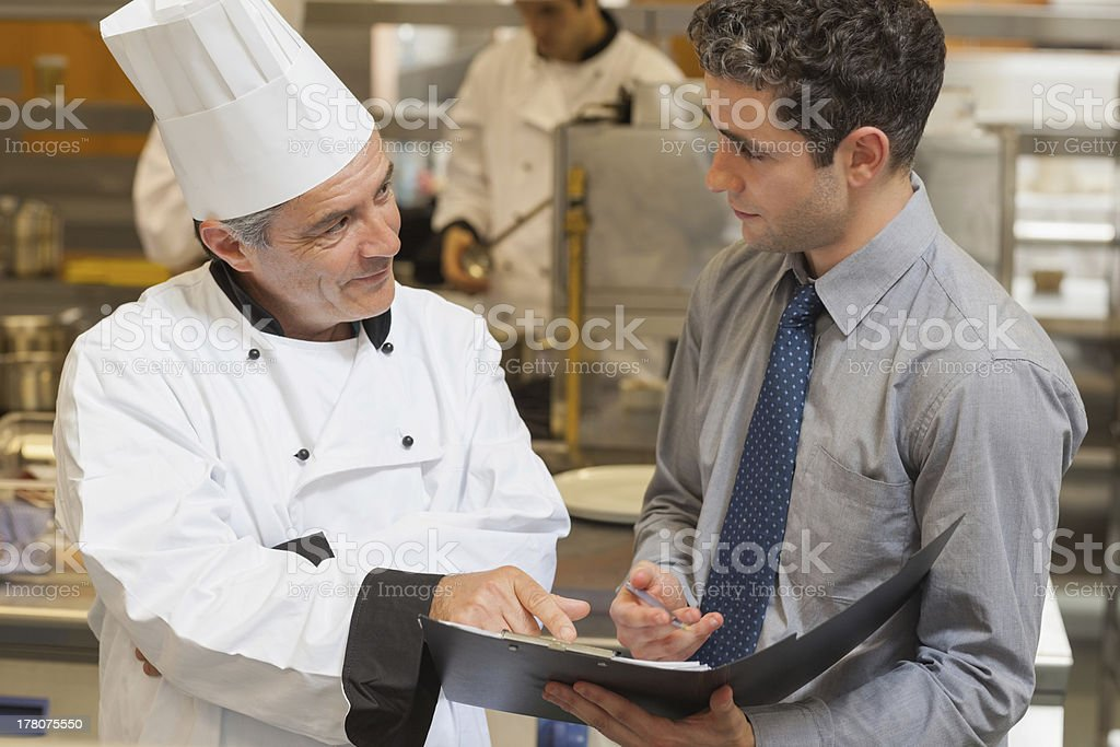 Waiter and chef discussing the menu stock photo
