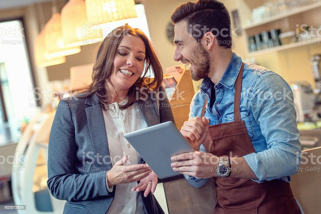 Waiter and customer smiling while looking at digital menu stock photo