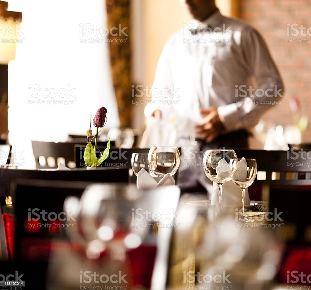 Waiter and Empty dining room of fancy restaurant stock photo